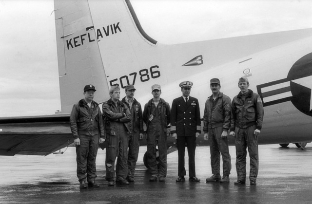 Members of the flight crew and the base commanding officer pose for a photo in front of a C-117 Skytrain aircraft parked on the flight line.  The aircraft is about to make it's last flight