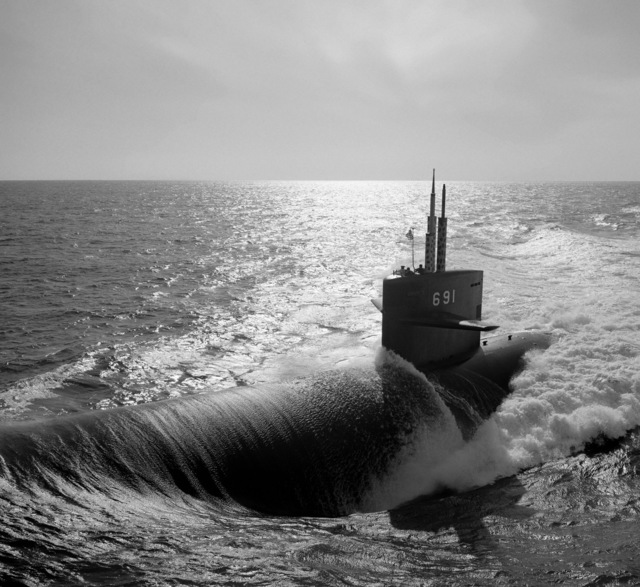 An aerial port bow view of the nuclear-powered attack submarine USS MEMPHIS (SSN 691) underway