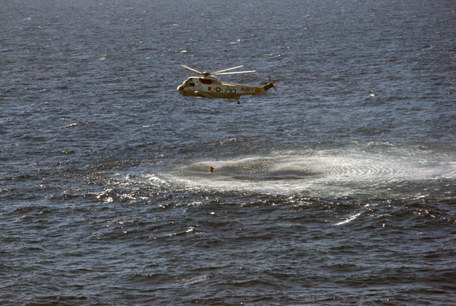 A Helicopter Anti-submarine Squadron 11 (HS-11) SH-3H Sea King helicopter hovers over the downed pilot of an A-7E Corsair II aircraft that crashed after being launched from the nuclear-powered aircraft carrier USS DWIGHT D. EISENHOWER (CVN 69)