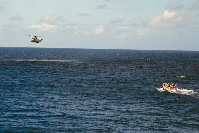 A Helicopter Anti-submarine Squadron 11 (HS-11) SH-3H Sea King helicopter hovers over the downed pilot of an A-7E Corsair II aircraft as a motor whatleboat arrives to help. The aircraft crashed after being launched from the nuclear-powered aircraft carrier USS DWIGHT D. EISENHOWER (CVN 69)