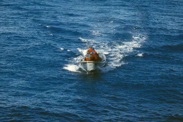 A motor whaleboat returns to the aircraft carrier USS DWIGHT D. EISENHOWER (CVN 69) after picking up the pilot of an A-7E Corsair II that crashed into the ocean after launch