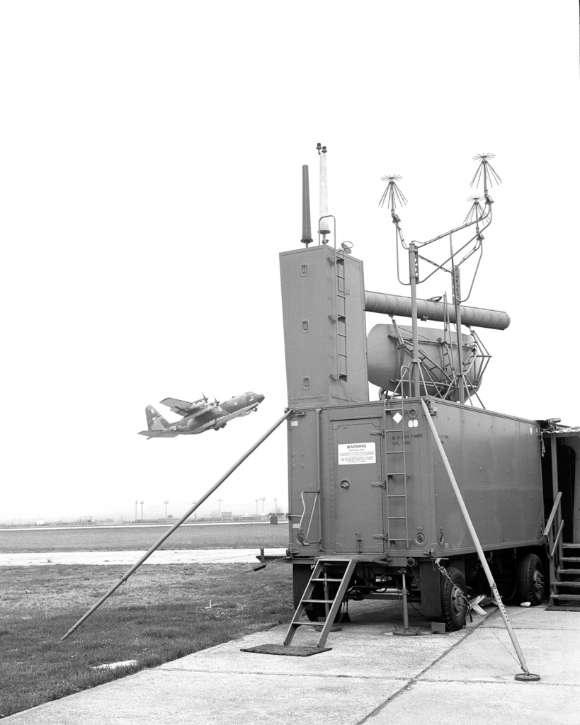 A view of a radar installation operated by the 2187th Communications Group, with a C-130 Hercules aircraft taking off in the background