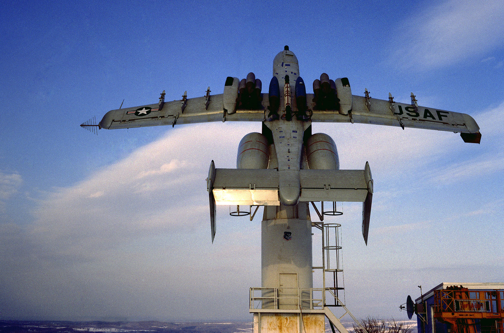 An A-10 Thunderbolt II aircraft with an assortment of weapons stores is secured atop a 30-foot pedestal at the Rome Air Development Center's Newport Test Site. A new configuration of weapons will alter the effectiveness of the aircraft's antennas. The tests being conducted will assess antenna effectiveness