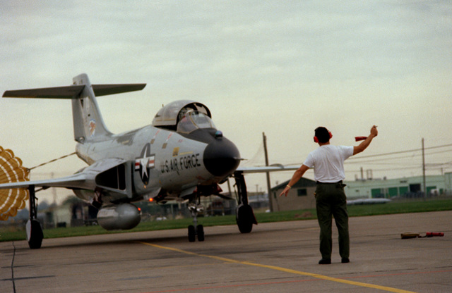 A ground crew chief marshals an F-101 Voodoo aircraft into a parking position. The aircraft is assigned to the 107th Fighter Interceptor Group, New York Air National Guard, North American Air Defense Command (NORAD)