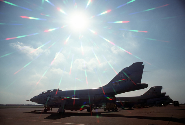 A left rear view of an F-101 Voodoo aircraft parked with other F-101s. The aircraft are silhouetted against an afternoon sun. The aircraft are assigned to the 107th Fighter Interceptor Squadron, New York Air National Guard, North American Air Defense Command (NORAD)
