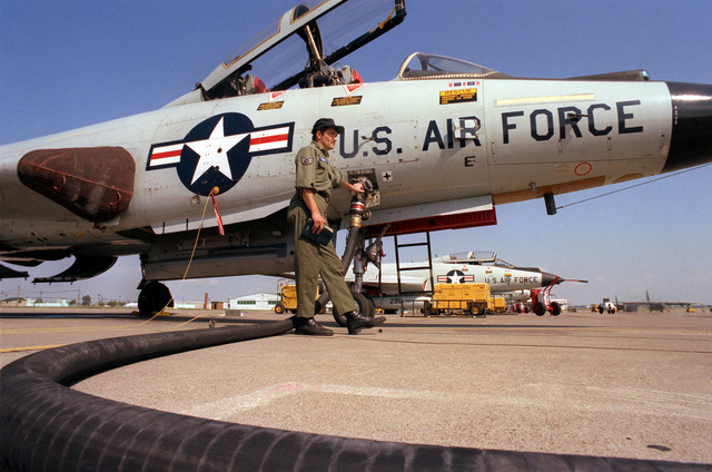 A staff sergeant refuels an F-101 Voodoo aircraft from a fuel truck. Other F-101s are in the background