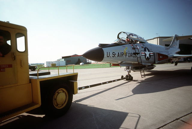 A vehicle tows an F-101 Voodoo aircraft from a hangar. The aircraft is assigned to the 107th Fighter Interceptor Squadron, New York Air National Guard, North American Air Defense Command (NORAD)