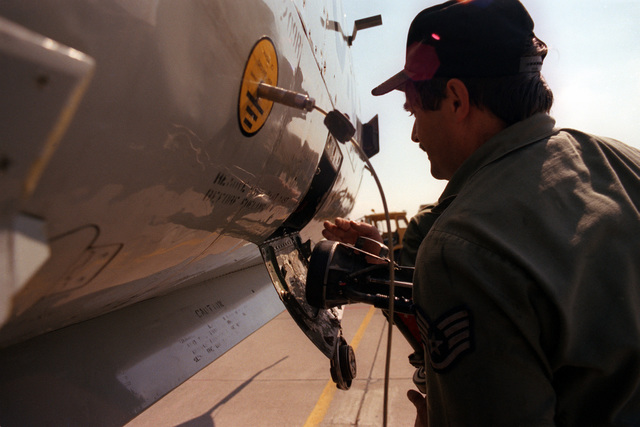 Airmen insert a refueling nozzle into a F-101 Voodoo aircraft