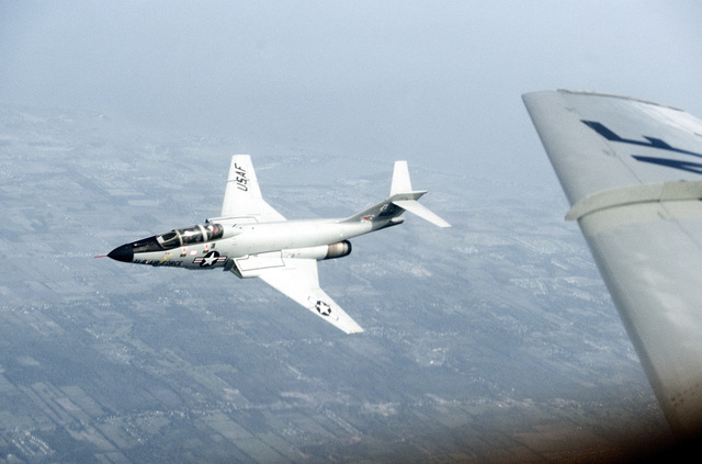 AN air-to-air left front view of an F-101 Voodoo aircraft banking to the left in flight. The wing of another F-101 as seen in the foreground. The aircraft is assigned to the 107th Fighter Interceptor Group, New York Air National Guard, North American Air Defense Command (NORAD)