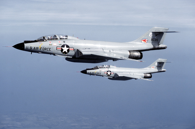 AN air-to-air left side view of two F-101 Voodoo aircraft in flight. The aircraft are assigned to the 107th Fighter Interceptor Group, New York Air National Guard, North American Air Defense Command (NORAD)