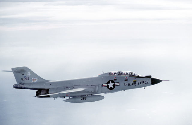 AN air-to-air side view of an F-101 Voodoo aircraft in flight. The aircraft is assigned to the 107th Fighter Interceptor Group, New York Air National Guard, North American Air Defense Command (NORAD)