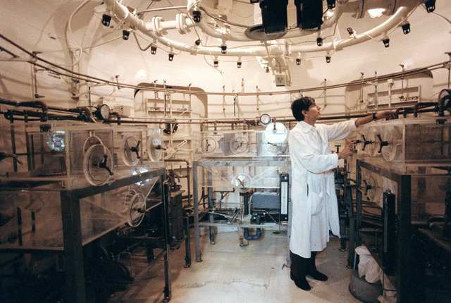 Chemist Joe Diaz works in an interconnecting air lock which is under one of Thomas Domes. The dome is part of the Air Force Aerospace Medical Research Laboratory, Aerospace Medical Division, Air Force Systems Command