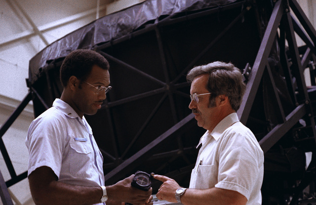 Second LT. John Alston (right), speaks with Lear Siegler Inc. employee Russell Hitchcock about a malfunctioning component of a fighter-bomber flight simulator. Alston works in the Flight Control Development Laboratory, Flight Dynamics Laboratory, Flight Control Division, Air Force Systems Command