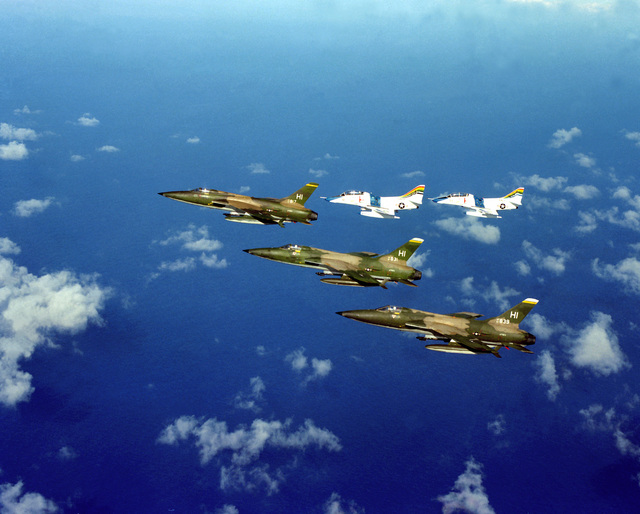 An air-to-air left side view of three F-105 Thunderchief aircraft from 508th Tactical Air Force Reserve Unit and two TA-4J Skyhawk aircraft from Fleet Composite Squadron 1 (VC-1) flying in formation