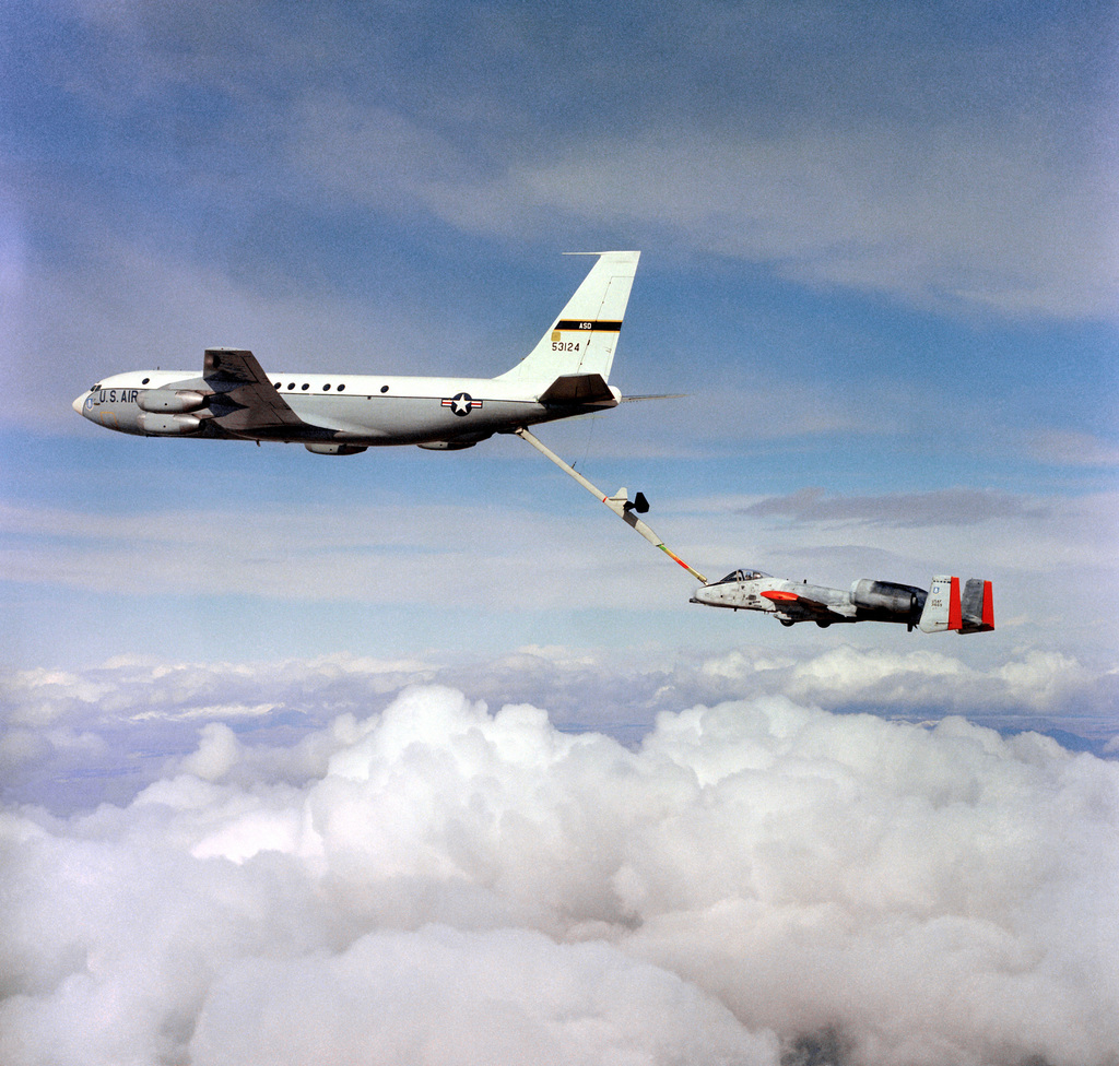 An air-to-air left side view of an A-10 Thunderbolt II aircraft being refueled by a KC-135A Stratotanker aircraft. The Advanced Aerial Refueling Boom is attached between the two aircraft