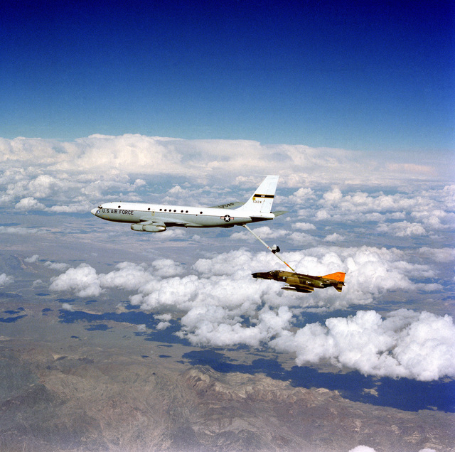 An air-to-air left side view of an F-4 Phantom II aircraft being refueled by a KC-135A Stratotanker aircraft. The Advanced Aerial Refueling Boom is attached between the two aircraft