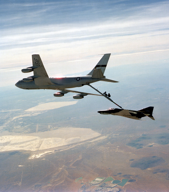 An air-to-air left side view of an RF-4C Phantom II aircraft being refueled by a KC-135A Stratotanker aircraft. The advanced aerial refueling boom is attached between the two aircraft