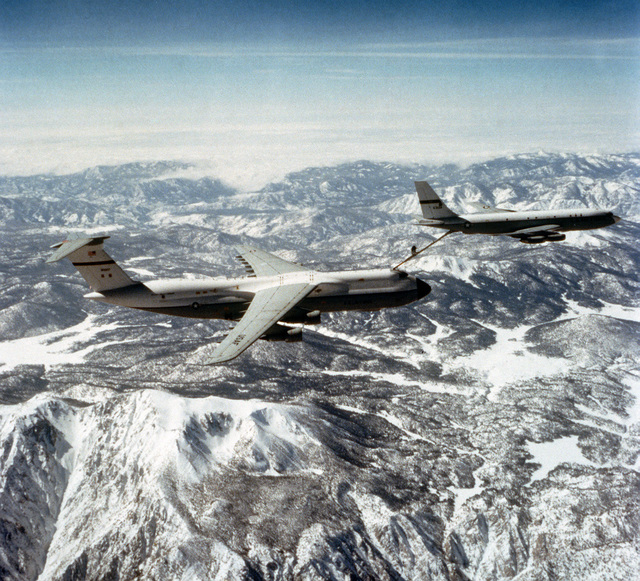 An air-to-air right side view of a C-5A Galaxy aircraft being refueled by a KC-135A Stratotanker aircraft. The Advanced Aerial Refueling Boom is attached between the two aircraft