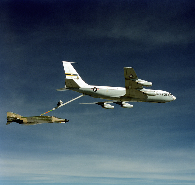 An air-to-air right side view of an F-4 Phantom II aircraft being refueled by a KC-135A Stratotanker aircraft. The Advanced Aerial Refueling Boom is attached between the two aircraft