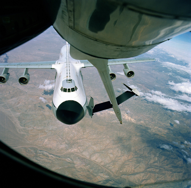 An air-to-air view of a C-5A Galaxy aircraft being refueled by a KC-135A Stratotanker aircraft. A view is taken from the Advanced Aerial Refueling Boom section of the KC-135A