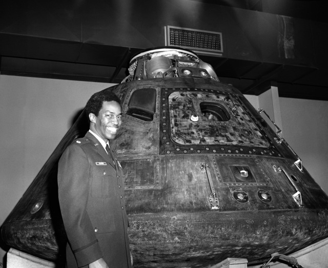 Astronaut selectee Major Guion S. Bluford Jr. stands beside the Apollo 15 capsule during a tour of the Air Force Museum