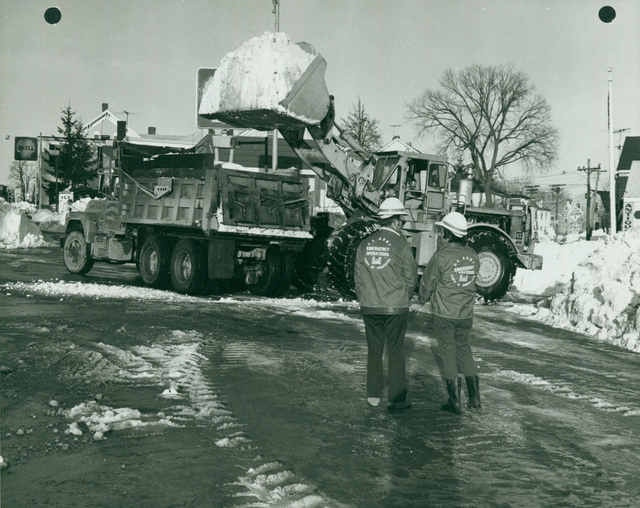 Front Loader Loading Snow into a Dump Truck during Cleanup Efforts after the Blizzard of 1978 in New England