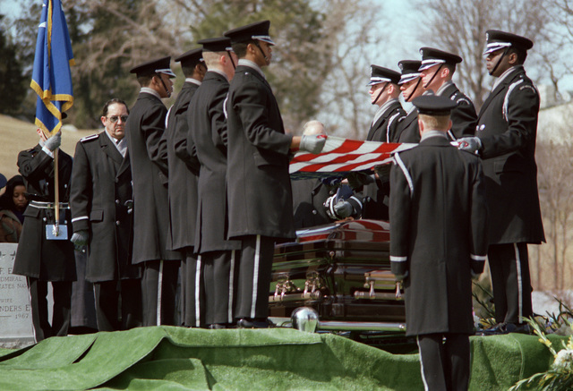 Honor Guard pallbearers undrape a U.S. flag from the casket before the burial at Arlington National Cemetery of GEN Daniel (Chappie) James. The funeral was conducted in the Shrine of the Immaculate Conception at Catholic University