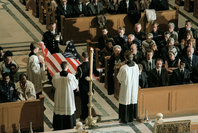 Honor Guard pallbearers undrape a U.S. flag from the casket of GEN Daniel (Chappie) James in preparation for Requiem Mass by priests. The funeral is being conducted in the Shrine of the Immaculate Conception at Catholic University
