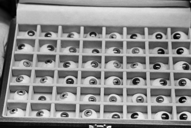 A close-up view of a box containing various sizes and shapes of prosthetic eyes in the dental lab on board the Navy's newest hospital ship USNS MERCY (T-AH 19).  Dental technicians do all facial prosthetic work because the materials used are the same as those used to make dentures
