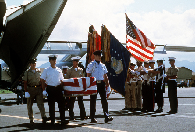 Joint-service pallbearers transfer flag-draped coffins of missing in action (MIA) soldiers to buses upon the arrival in Hawaii of the airlift returning them from Vietnam