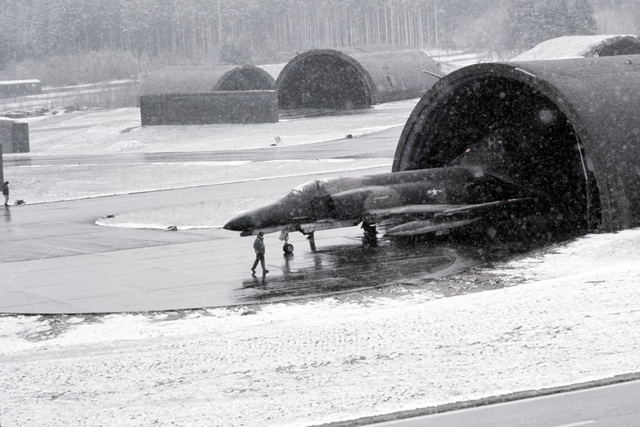 Flight line personnel wait for snowy conditions to clear prior to guiding an F-4 Phantom II aircraft out onto the runway during Exercise SALTY ROOSTER