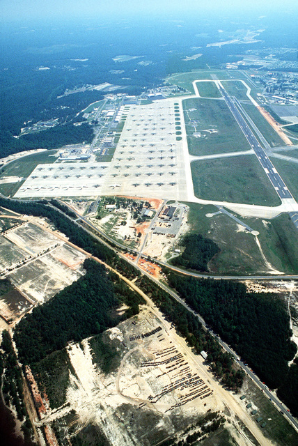 An aerial view of C-141 Starlifter and C-130 Hercules aircraft parked on the flight line during the Zaire alert build-up. Equipment of the 82nd Airborne Division is staged in a field in the foreground