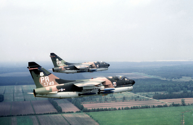 An air-to-air right side view of two Puerto Rico Air National Guard A-7D Corsair II aircraft in formation during Exercise Solid Shield '78. The aircraft are armed with Mark 82 500-pound bombs