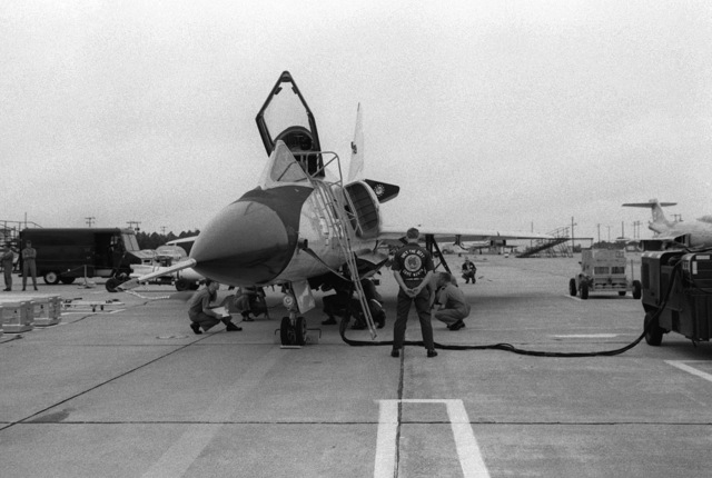 Inspectors observe closely as personnel of the 5th Fighter Interceptor Squadron attach a cable to an AIM-4G Super Falcon missile aboard an F-106 Delta Dart aircraft during the 1978 North American Aiar Defense Command Weapons Loading Competition