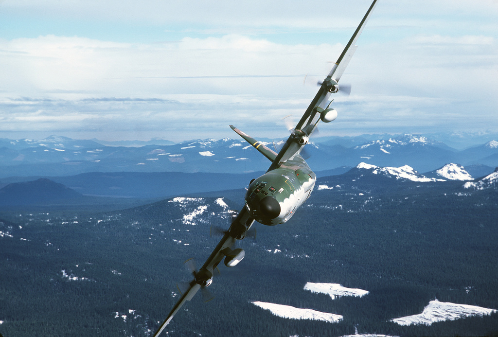 An air-to-air front view of a 36th Tactical Airlift Squadron C-130E Hercules aircraft in a steep bank