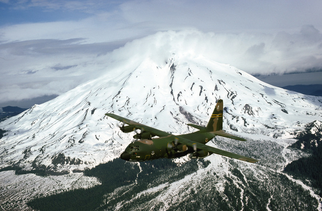 An air-to-air left front view of a 36th Tactical Airlift Squadron C-130E Hercules aircraft. Mount St. Helens is in the background