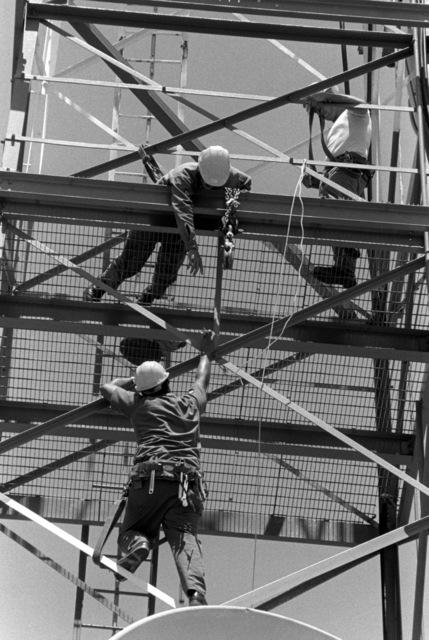 Civil engineering airmen repair a microwave communication tower disc