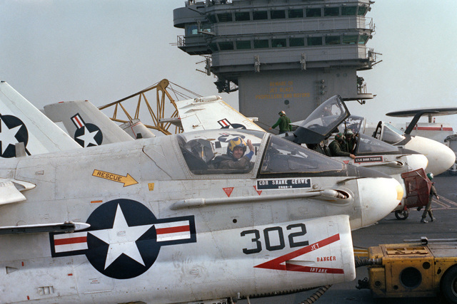 A pilot waves from the cockpit of an A-7E Corsair II aircraft on the flight deck of the nuclear-powered aircraft carrier USS DWIGHT D. EISENHOWER (CVN 69)