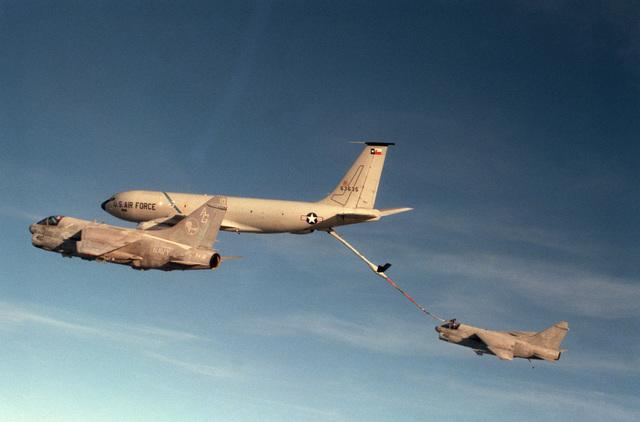An Air Force KC-135 Stratotanker aircraft refuels an Attack Squadron 12 (VA-12) A-7E Corsair II aircraft in flight as another VA-12 A-7E Corsair II flies alongside