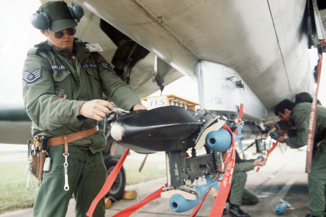 An Air Force staff sergeant loads practice bombs onto a 507th Tactical Fighter Group F-105 Thunderchief aircraft parked on the flight line