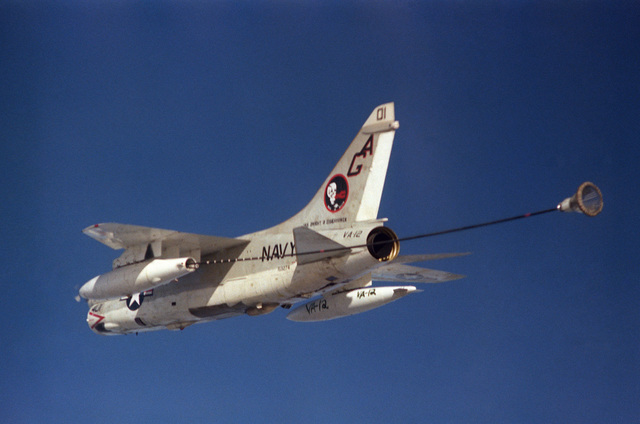 An air to air left rear view of an Attack Squadron 12 (VA-12) A-7E Corsair II aircraft trailing a refueling drogue from a buddy store