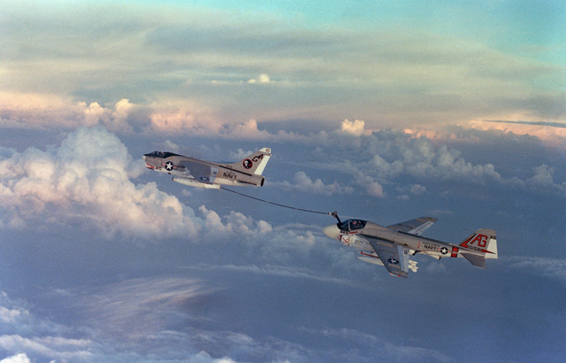 An air to air left rear view of an Attack Squadron 12 (VA-12) A-7E Corsair II aircraft trailing a refueling drogue from a buddy store to refuel an Attack Squadron 65 (VA-65) Intruder aircraft