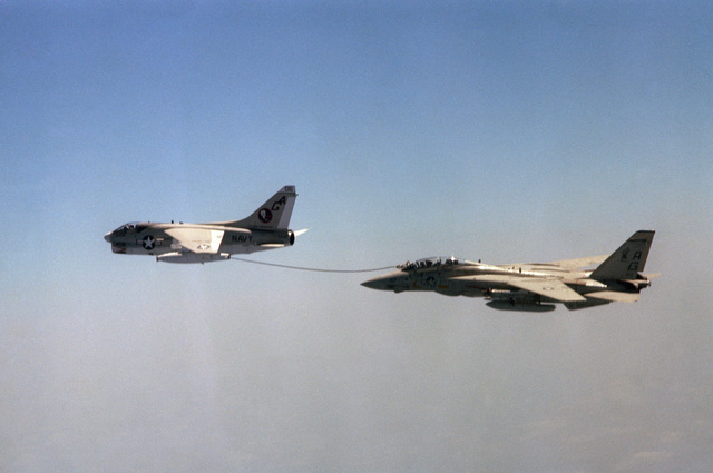 An air to air left side view of an Attack Squadron 12 (VA-12) A-7E Corsair II aircraft trailing a refueling drogue from a buddy store to refuel a Fighter Squadron 143 (VF-143) F-14A Tomcat aircraft