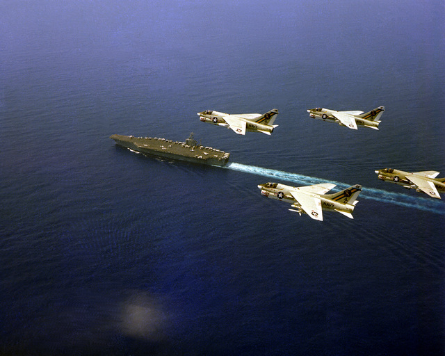 An air-to-air left side view of four Attack Squadron 66 (VA-66) A-7E Corsair II aircraft in formation above the nuclear-powered aircraft carrier USS DWIGHT D. EISENHOWER (CVN-69)