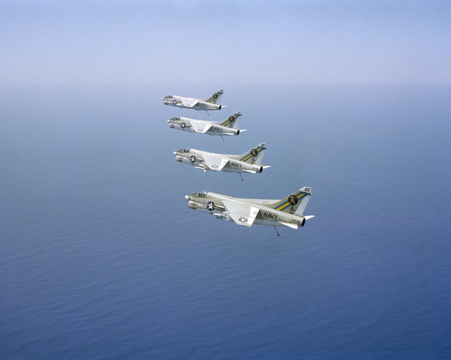 An air to air left side view of four Attack Squadron 66 (VA-66) A-7E Corsair II aircraft in formation with arresting gear hooks extended