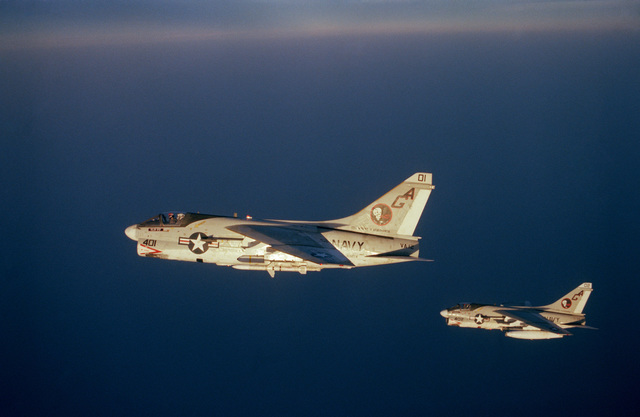 An air to air left side view of two Attack Squadron 12 (VA-12) A-7E Corsair II aircraft. The aircraft to the left is armed with an AGM 45 Shrike and an AIM-9 Sidewinder missile