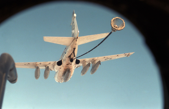An air to air rear view of a KA-6D Intruder aircraft trailing a refueling drogue. The refueling probe of another aircraft is on the left