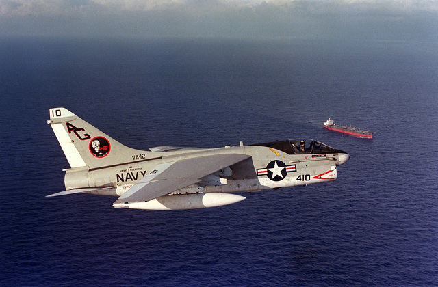 An air-to-air right side view of an Attack Squadron 12 (VA-12) A-7E Corsair II aircraft. In the background is an unidentified commercial oil tanker