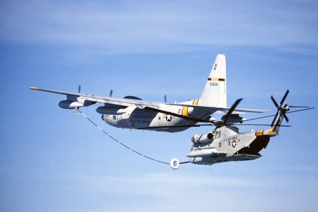 An air-to-air left side view of an HC-130 Hercules aircraft refueling a 39th Aerospace Rescue and Recovery Wing HH-53 helicopter off the coast of Greenland. The HH-53 is en route from Eglin Air Force Base, Florida, to Woodbridge, England