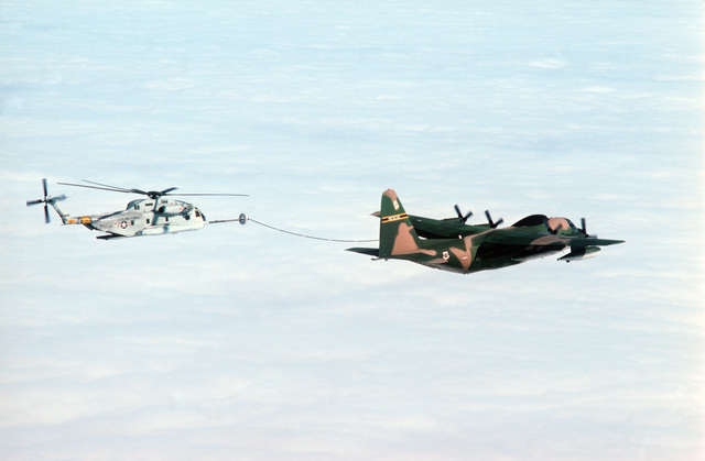 An air-to-air left side view of HC-130 Hercules aircraft refueling a 39th Aerospace Rescue and Recovery Wing HH-53 helicopter off the coast of Greenland.  The HH-53 is en route from Eglin Air Force Base, Florida, to Woodbridge, England